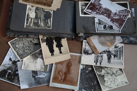 An open photo album and a scattering of loose black&white and sepia-toned photographs, mostly portraits and groups of people, that appear to be from the first half of the 20th century. No faces can be fully seen
