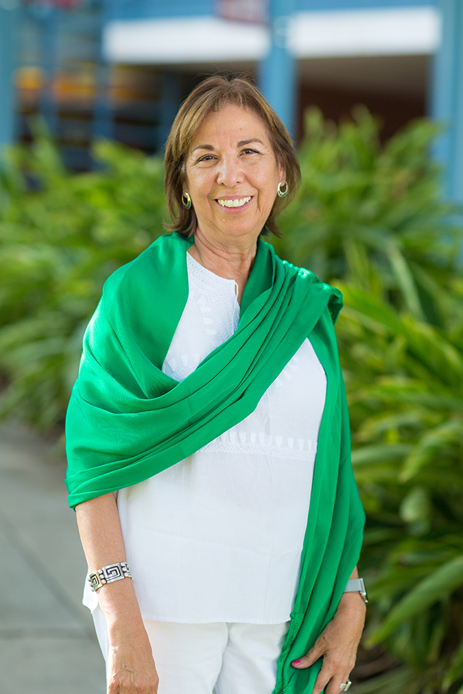 A woman stands, smiling at the camera, dressed in white and draped in a bright green scarf.