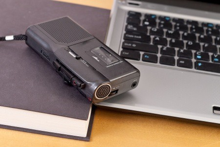 An audio recorder, a laptop, and a book with a black cover
