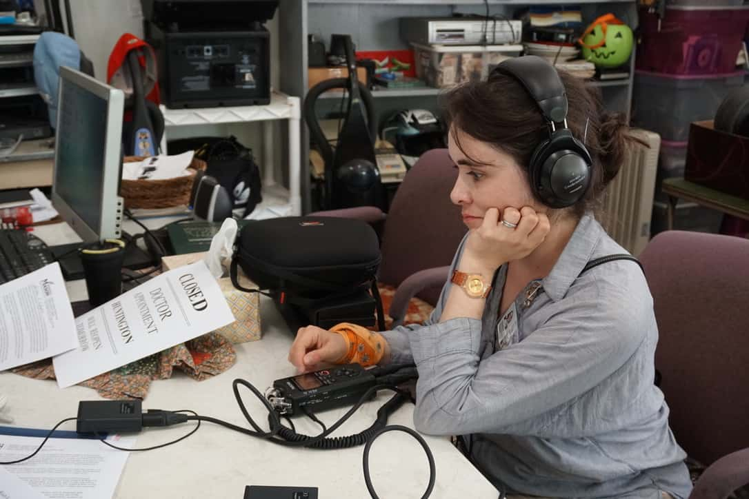 A woman in an office wearing headphones attached to an audio recorder