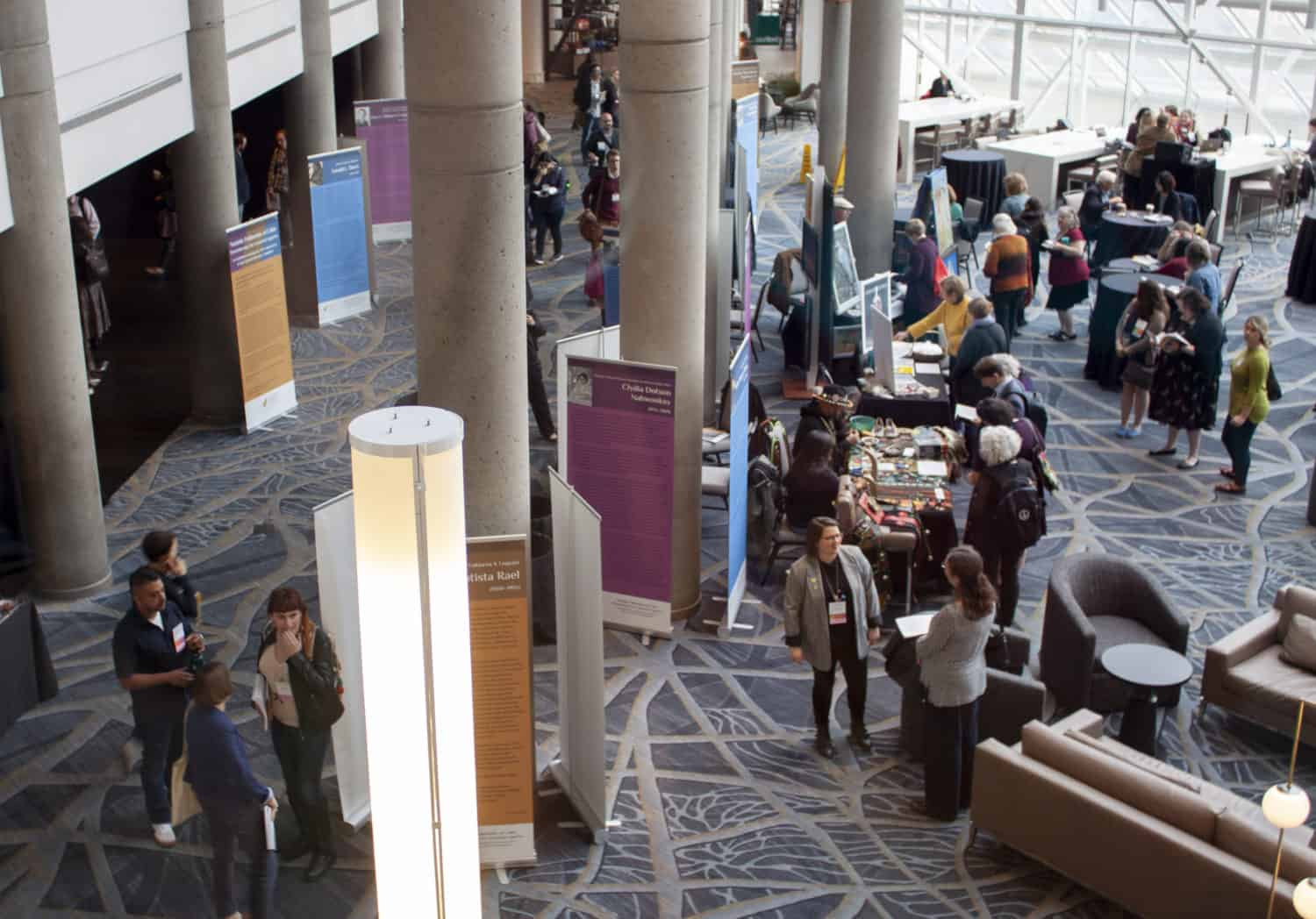 View from above of many people gathered in a hotel lobby around posters and exhibit tables
