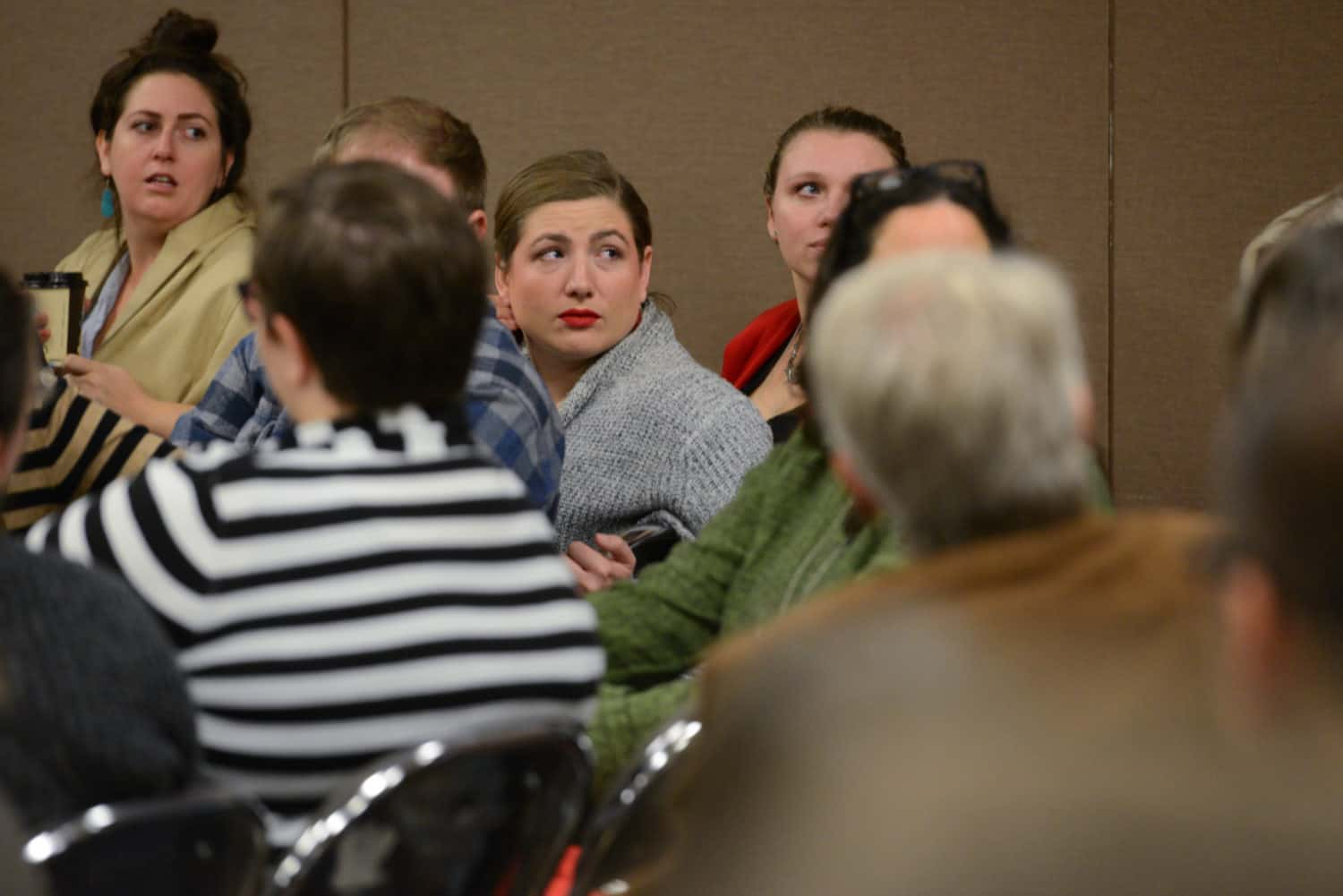 Audience members turn around to face a speaker in a conference panel audience