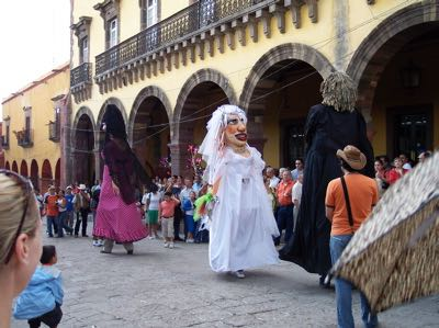 Giant masked figures in costume, including a female figure in a white veil and dress, in a courtyard with a crowd watching from the periphery
