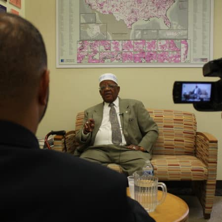We see over the shoulder of an interviewer and a videorecorder pointed at a man seated on a couch