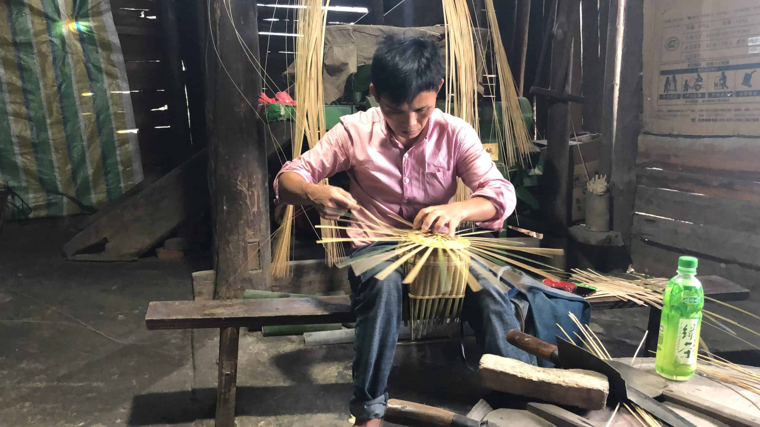 A man sitting on a bench making a basket from cane splits..