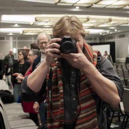A young man points a camera into the camera in a hotel ballroom. People chat in the background.