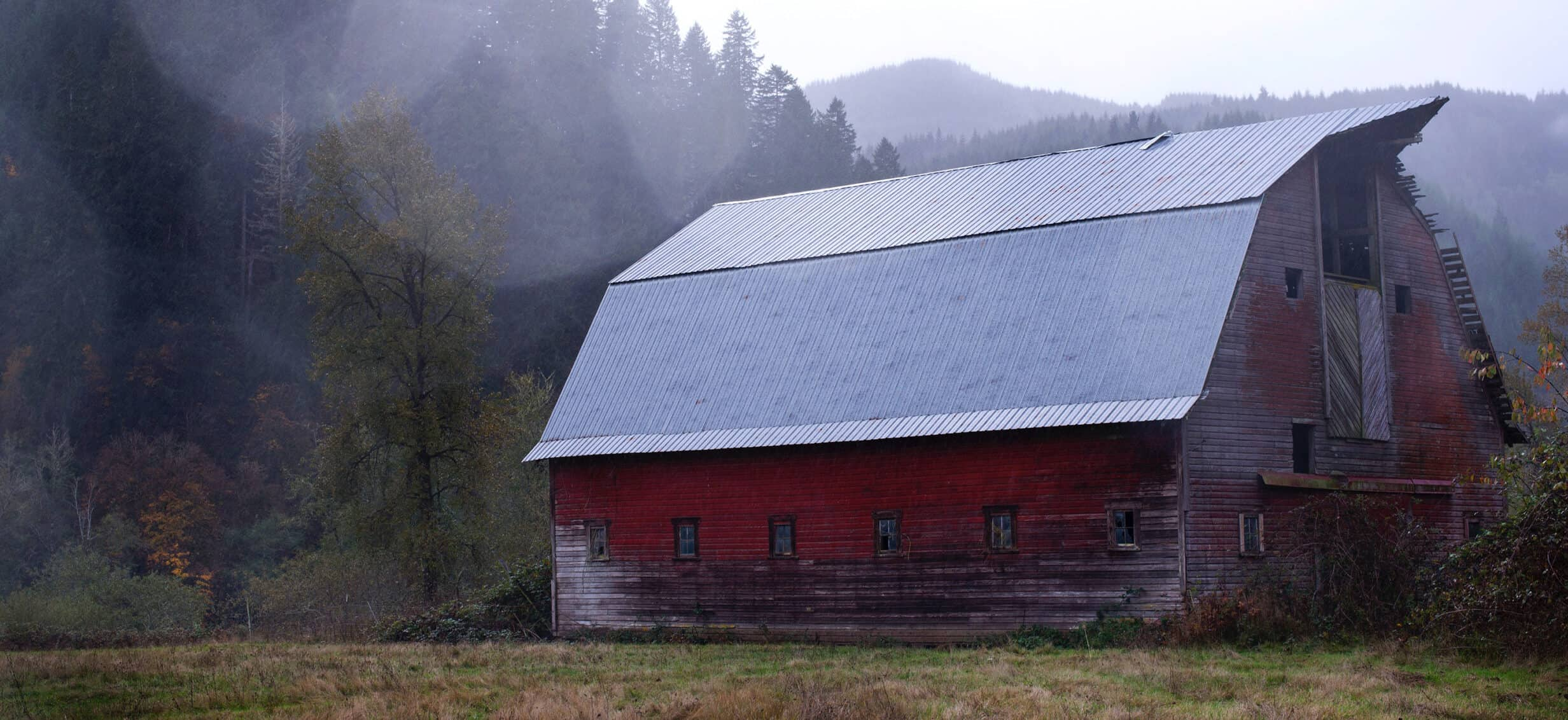 A large, red barn with a small mountain in the background and fog in the air.