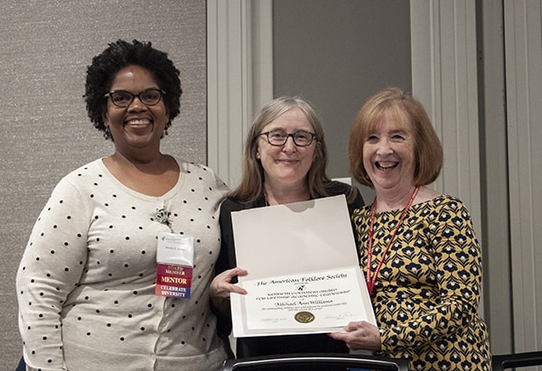 Three women stand, smiling at the camera, the center woman holds an award certificate.