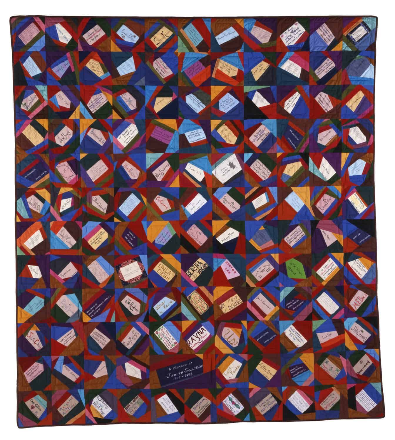 A square quilt made of irregularly shaped, colorful fabric pieces