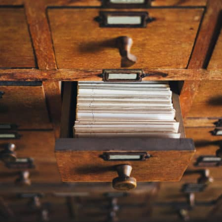 An open drawer in a wooden card catalog case shows the tops of cards