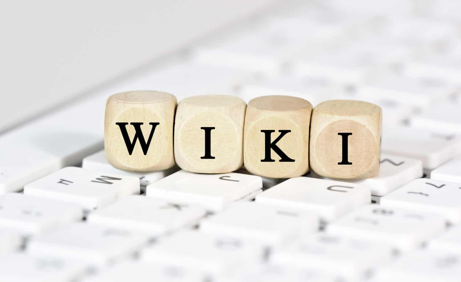 """Blocks with letters spell out """"wiki,"""" resting on a keyboard"""