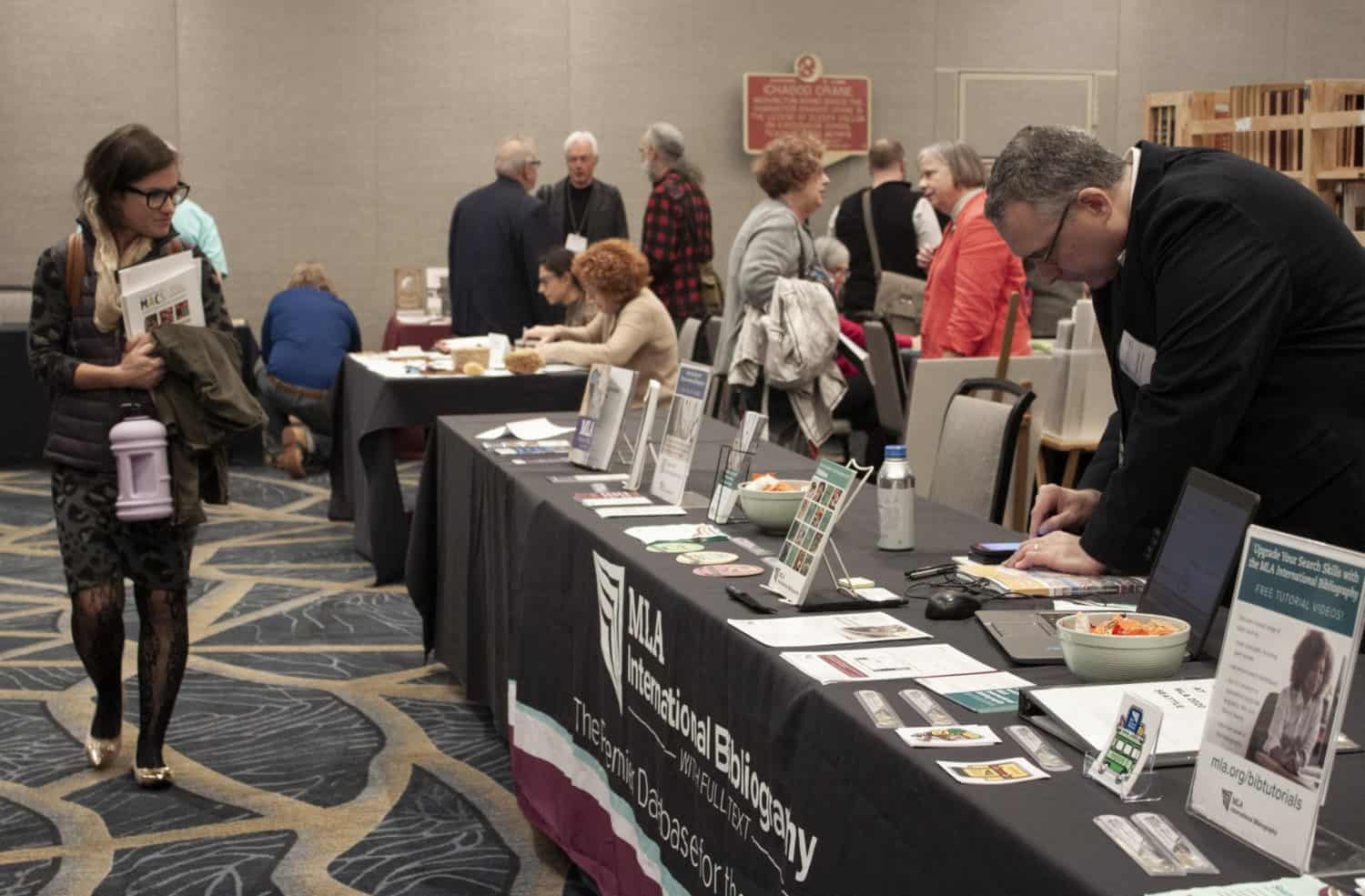 People browse and chat in groups around display tables in a conference exhibit room.