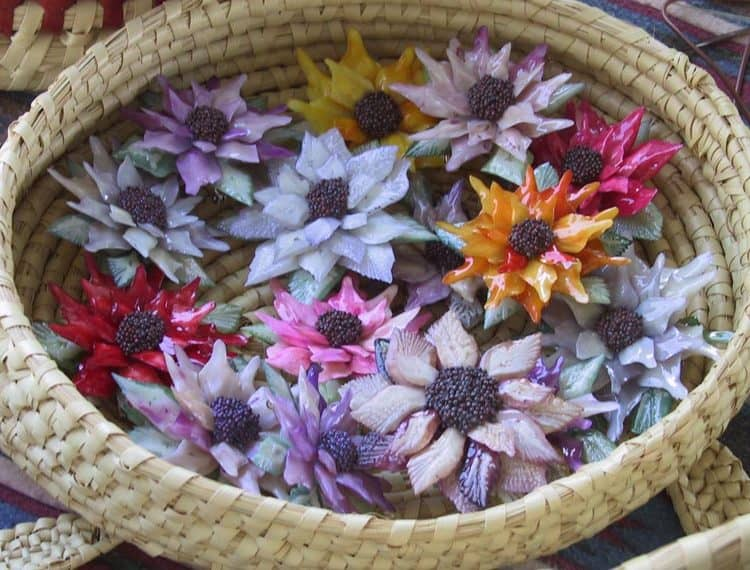 Small, colorful, flower head sculptures made from garfish scales.