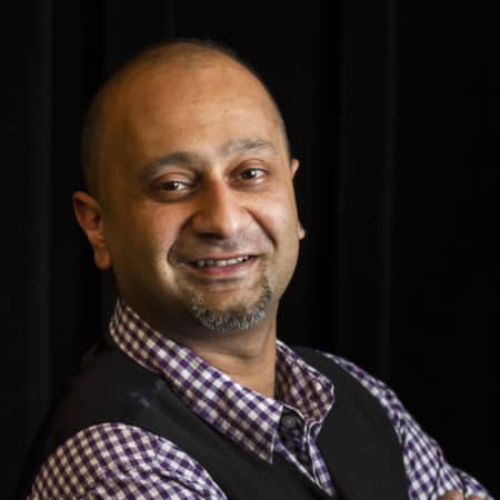 A headshot of a man smiling towards the camera.