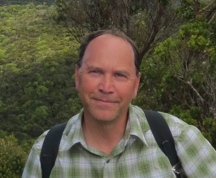 A man in a short-sleeved plaid shirt and carrying a backpack looks at the camera.