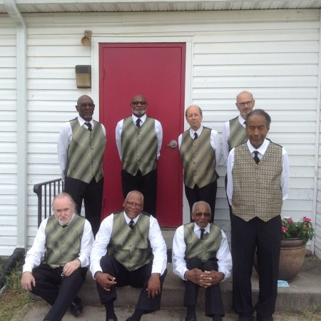 A group of eight men, similarly dressed in vests, button-down white shirts, and black ties, stand in front of a red church door.