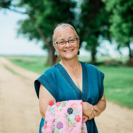 A woman stands on a dirt road, smiling at the camera.